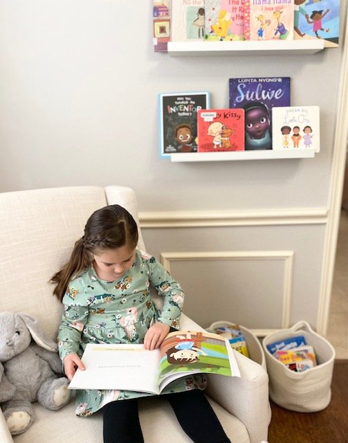 Charlotte reading thematic books in our play room reading corner