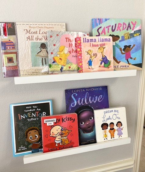 Our thematic books displayed on floating shelves in the play room